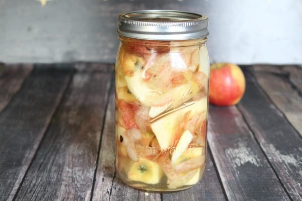 apple scraps in a glass jar fermenting to make apple cider vinegar with the mother